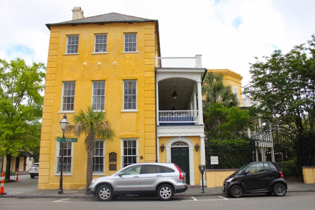 An old yellow house with three levels and two cars in the front
