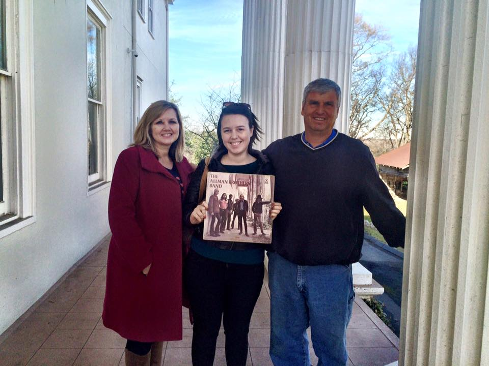 Three people hold an Allman Brothers record