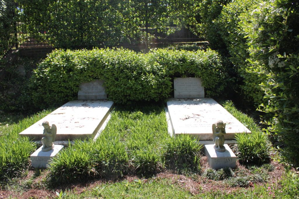 Two gravesites sit in a cemetery with angel statues